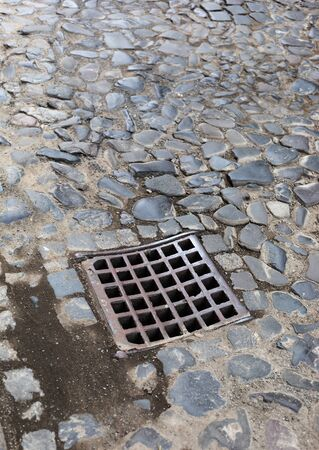 Old iron grate of the drainage system hatch on the road paved with paving stones