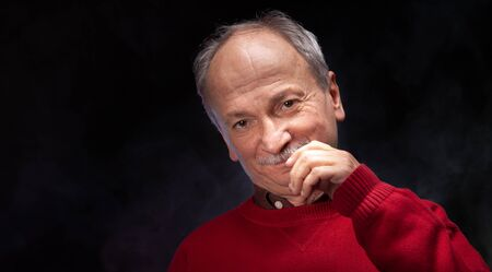 Studio portrait of an elderly man in a red sweater