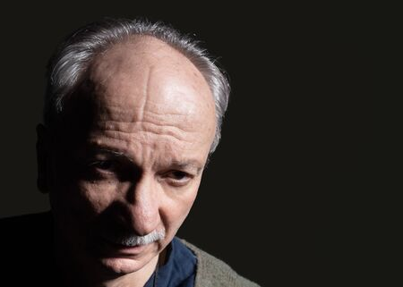 High contrast portrait with deep dark shadows of an elderly man on a dark background. Studio portrait of an old tired man on a dark background. Looks skeptical