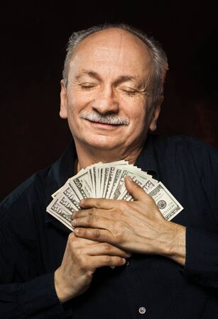 Senior gentleman holding a stack of money. Portrait of an excited old man. Happy old man holding dollar banknotes on dark red background.