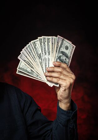 Men hand with a fan of dollar bills on a dark background