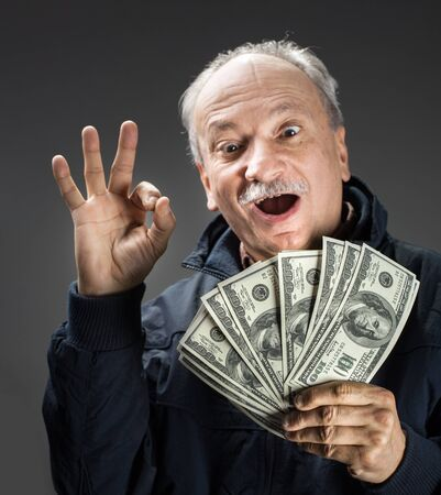 Senior gentleman holding a stack of money. Portrait of an excited old man. Happy old man holding dollar banknotes. 版權商用圖片