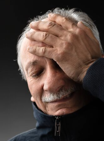 Portrait of an elderly man with a headache. Old man with infection and high temperature