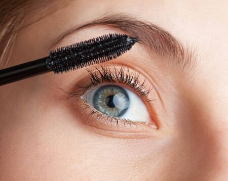Makeup and beauty concept. Beautiful woman applied mascara to her lashes