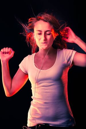 Beautiful Woman Listening Music. Attractive smiling happy woman dancing and listening to music in headphone on dark studio background, wearing white shirt. High contrast image in trendy neon colors 版權商用圖片