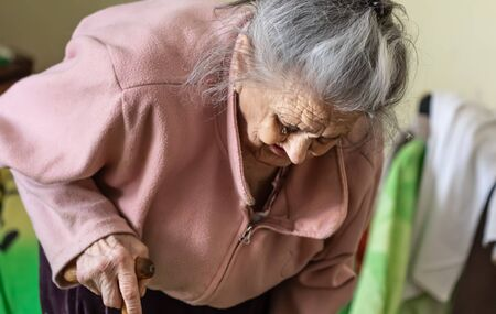 Old age concept. Portrait of a very old and tired of life wrinkled woman near the window in the bedroom of her house. Sad and depressed older woman alone