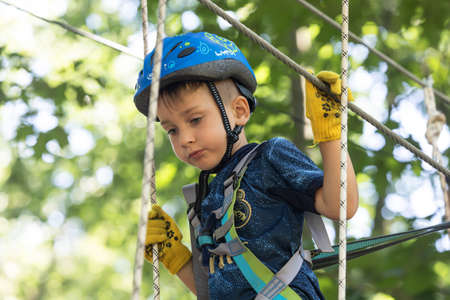 UZHHOROD, UKRAINE - Jul 23, 2020: Extreme sport in adventure park. Young boy passing the cable route high among trees Editorial