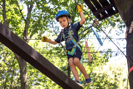 UZHHOROD, UKRAINE - Jul 23, 2020: Extreme sport in adventure park. Young boy passing the cable route high among trees