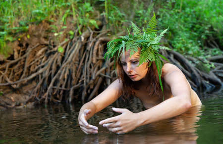 A beautiful young woman with fern wreath on her head enjoying nature in the forest river Standard-Bild