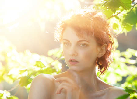 Portrait of a young red-haired woman among the foliage of trees illuminated by the suns rays