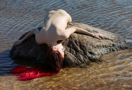 Young naked woman with scarlet dreadlocks lies on a stone on the sea 版權商用圖片