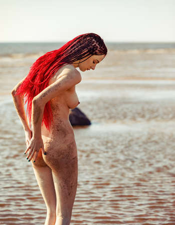 Young naked woman with scarlet dreadlocks enjoys nature by the sea 版權商用圖片