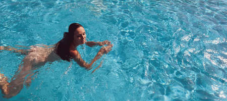 Naked woman outdoors. Beautiful young woman in swimming pool.