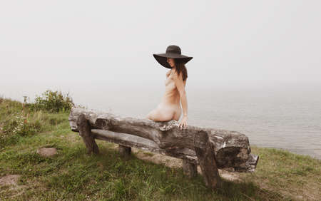Young woman sits on a wooden bench near a cliff by the sea on a foggy day