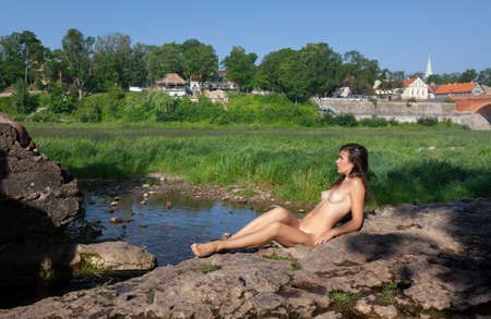 Young woman sunbathing on a stone near the river in an old provincial town
