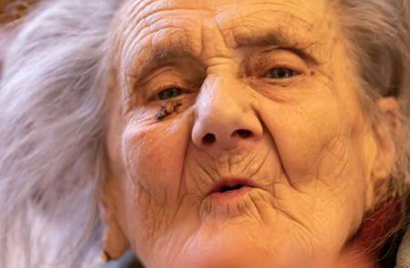 Old woman. Portrait of very old tired woman in depression sitting indoors on bed