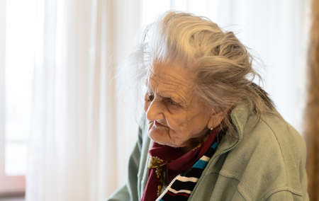 Old woman. Portrait of very old tired woman in depression standing near the window