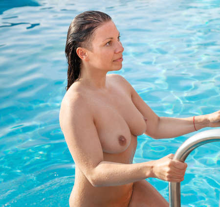 Nude woman outdoors. Healthy lifestyle. Young full fat woman with big coming out of the outdoor pool after a swim. Wet woman