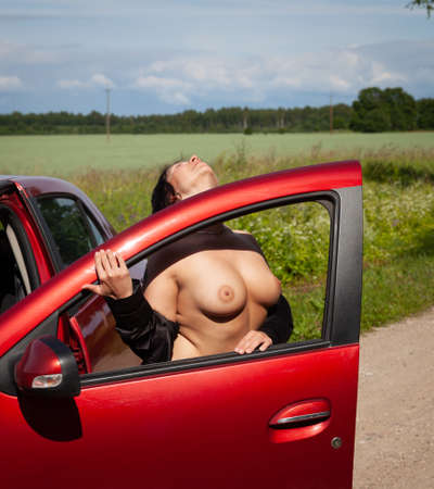 Beautiful brunette with large near the car. Sexy woman Stock Photo