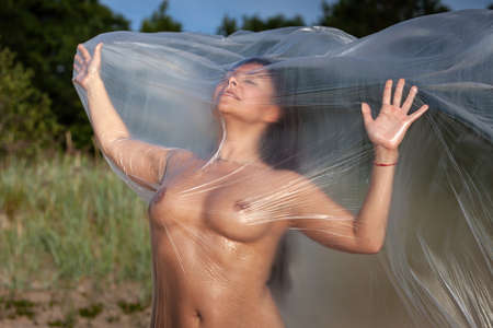 Beautiful body of woman on nature background under plastic wrap. Sexy girl behind a polyethylene film by the sea on a windy day. Fine-art photo. Banque d'images