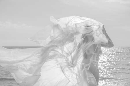 Beautiful body of woman on nature background under plastic wrap. Sexy girl behind a polyethylene film by the sea on a windy day. Fine-art photo.