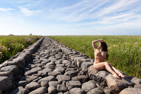 Young beautiful nude woman posing on a stone breakwater. Naked brunette enjoying nature