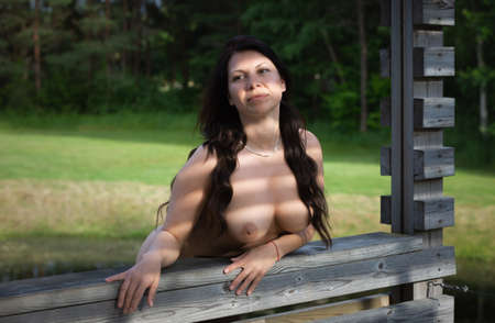 Beauty and lifestyle concept. Young naked woman posing near a wooden gazebo in nature