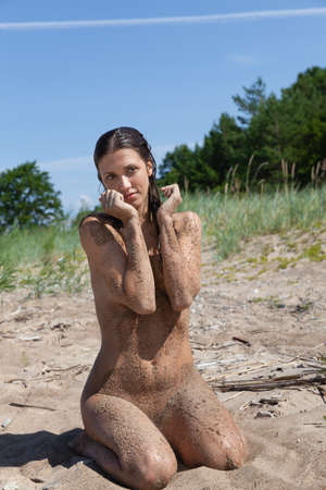 Beauty Girl Outdoors enjoying nature. Healthy lifestyle concept. Young naked woman covered by sand resting on a sandy beach
