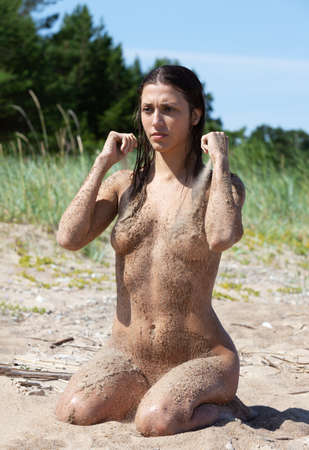 Beauty Girl Outdoors enjoying nature. Healthy lifestyle concept. Young naked woman covered by sand resting on a sandy beach Banco de Imagens - 164293589