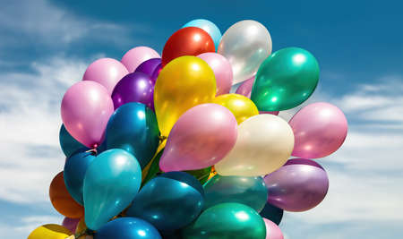 Lots of colorful balloons on the blue sky background with clouds