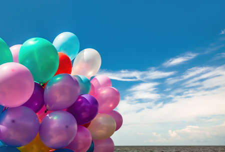 Lots of colorful balloons on the blue sky background with clouds and sea Banco de Imagens