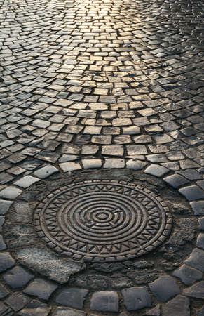 Streets of the old town. Sewer hatch. Stone paving texture. Abstract structured background. Banco de Imagens