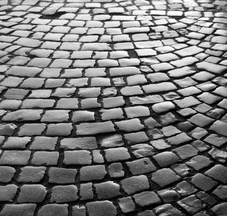 Streets of the old town. Stone paving texture. Abstract structured background. Black and white image