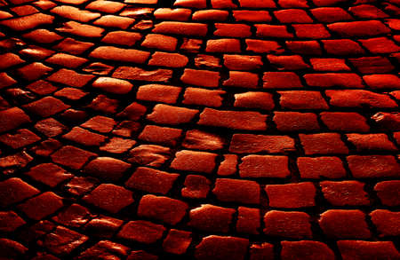Streets of the old town. Stone paving texture. Abstract structured background. Image in a dramatic dark red tone