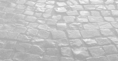 Streets of the old town. Stone paving texture. Abstract structured background. Image in light gray tonality Banco de Imagens