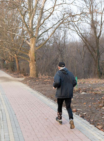 Healthy and active lifestyle concept. An elderly sporty man runs along the park alley during morning workout.