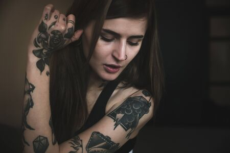Young tattooed woman with long hair poses, looking down Stock fotó