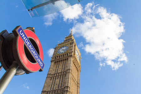constitute: London, United Kingdom - May 23, 2004:  Shot taken from a bus stop of a London Underground Tube sign and the Big Ben on Elizabeth Tower in the Palace of Westminster. These constitute some of Londons principal icons, widely recognized worldwide.