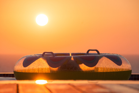 float tube: Inflatable Swim Ring on a Swimming Pool Deck overlooking Pomos sea with Sun Setting