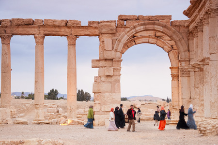 syrian: Palmyra, Syria-  November 28, 2008: Visitors walking in the Ruins of the ancient city of Palmyra, Syrian Desert.