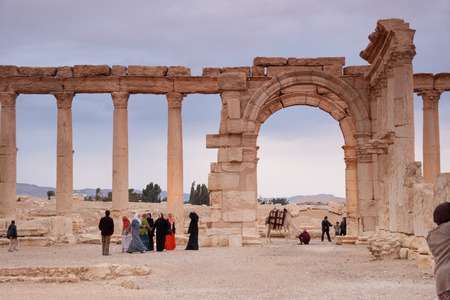 attested: Palmyra, Syria- November 28, 2008: Visitors in the Ruins of the ancient city of Palmyra, Syrian Desert Dating back to the Neolithic era, the city of Palmyra, was a strategically located oasis first attested in the early second millennium BC as a caravan s Editorial