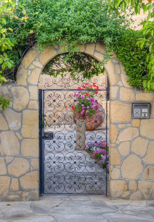 comprising: HDR processed shot of a beautiful traditional house entrance comprising an iron door in a traditional residential area of Nicosia, capital of Cyprus.