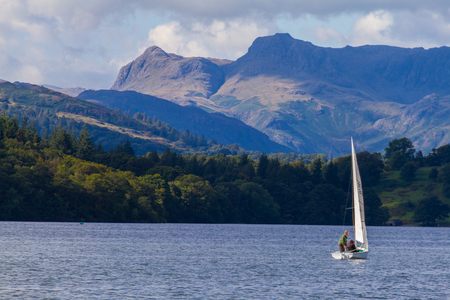 langdale: Sailboat in Lake Windermere,  Cumbria, UK, with the forest and mountains in the background shot during a boat trip on the lake