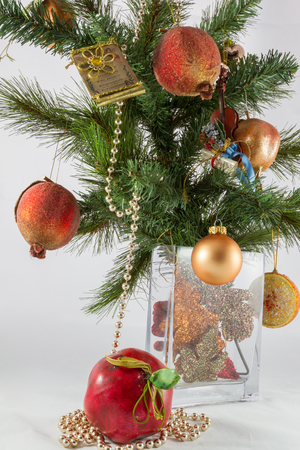 partition musique: Christmas tree branch and decoration in a vase including artificial pomegranates and apple