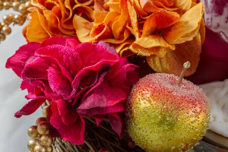 comprising: Traditional Christmas decoration comprising artificial apples, leaves, berries and flowers Stock Photo