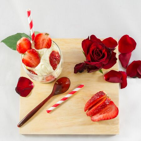 Strawberry ice-cream, rose flower and spoon on wooden board composition- top view