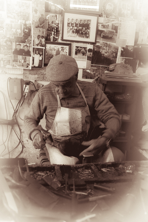 febuary: Cobbler at work practicing his craftmanship with traditional tools in old Nicosia, Cyprus. Toned photo taken in Febuary, 2016 Stock Photo