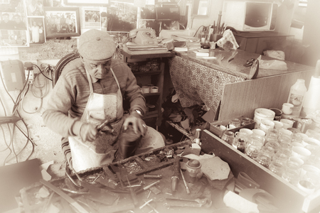 Cobbler at work practicing his craftmanship with traditional tools in old Nicosia, Cyprus. Toned photo taken in Febuary, 2016 Stok Fotoğraf