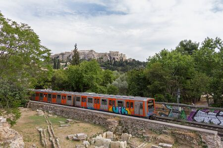 roman pillar: Passing train through Athens Ancient Agora with Acropolis in the background. Photo taken in spring 2016 Editorial