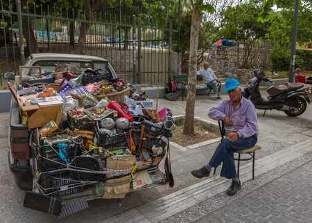 half stuff: Athens, Greece - April 30, 2016: A half-asleep old person next to a van full of old stuff near the Ancient Agora, Athens, Greece Editorial